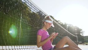 Menina do esporte que senta-se em um campo de tênis perto da rede e que usa o telefone esperto video estoque