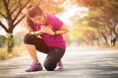 A menina do esporte tem a dor no peito após movimentar-se ou correndo dar certo no parque Conceito do esporte e dos cuidados médi foto de stock