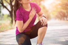 A menina do esporte tem a dor no peito após movimentar-se ou correndo dar certo no parque Conceito do esporte e dos cuidados médi fotografia de stock