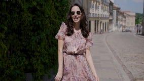A menina do estilo do moderno da forma anda através das ruas da cidade do verão filme