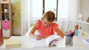 Menina do estudante com escrita do livro ao caderno em casa filme