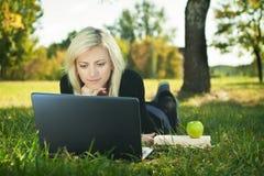 Menina do estudante com estudo do portátil Fotografia de Stock Royalty Free