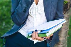 A menina do estudante com folhas do estudo e o glossário registram o close-up Foto de Stock
