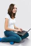 Menina do estudante com o laptop no fundo cinzento imagem de stock