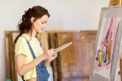Menina do estudante com pintura da armação na escola de arte Imagens de Stock Royalty Free