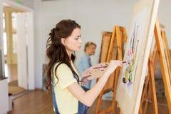 Menina do estudante com pintura da armação na escola de arte Foto de Stock Royalty Free