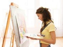 Menina do estudante com pintura da armação na escola de arte Fotografia de Stock