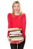 Menina do estudante com uma pilha de livros pesados Fotografia de Stock