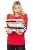 Menina do estudante com uma pilha de livros pesados Fotografia de Stock Royalty Free
