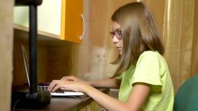 Menina do estudante que aprende na linha com um portátil branco que senta-se em uma tabela em sua sala adolescente No tempo da no filme