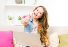 Menina do estudante que faz o polegar acima do gesto, sentando-se no sofá Fotos de Stock Royalty Free