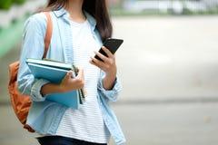 Menina do estudante que guarda livros e que usa o smartphone, educa??o em linha, uma comunica??o da tecnologia foto de stock royalty free