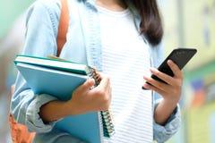 Menina do estudante que guarda livros e que usa o smartphone, educa??o em linha, uma comunica??o da tecnologia fotografia de stock