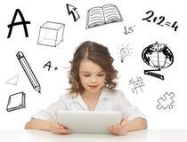 Menina do estudante que joga com PC da tabuleta Fotos de Stock