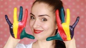 Menina do estudante do retrato que sorri e que mostra as mãos coloridas pintadas Conceito - felicidade, arte, humor criativo, bom vídeos de arquivo