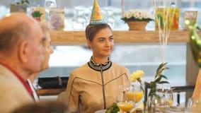 Menina do feliz aniversario em um tampão na cabeça da tabela no jantar vídeos de arquivo