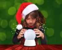 Menina do feriado que olha em um globo da neve do Natal Imagens de Stock Royalty Free