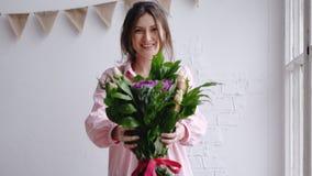 A menina do florista olha a câmera e mostra o ramalhete Retrato em um florista fotografia de stock