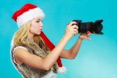Menina do fotógrafo em imagens do tiro do chapéu de Papai Noel Imagens de Stock Royalty Free