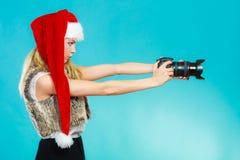 Menina do fotógrafo em imagens do tiro do chapéu de Papai Noel Fotografia de Stock Royalty Free