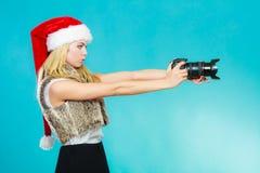 Menina do fotógrafo em imagens do tiro do chapéu de Papai Noel Imagens de Stock