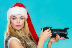 Menina do fotógrafo em imagens do tiro do chapéu de Papai Noel Fotografia de Stock