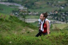 A menina do fotógrafo escala uma montanha Imagens de Stock Royalty Free