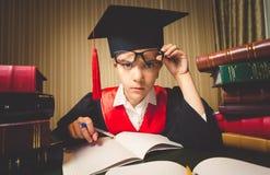 A menina do gênio no tampão da graduação que olha através dos monóculos em veio fotografia de stock royalty free