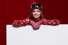 Menina do inverno que guarda um quadro de mensagens branco Foto de Stock