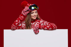 Menina do inverno que guarda um quadro de mensagens branco imagens de stock