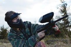 Menina do jogador do esporte do Paintball no uniforme e na máscara protetores da camuflagem fotografia de stock royalty free
