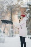 A menina do jovem adolescente limpa a neve perto da casa, guardando uma pá e a pá passa o tempo Foto de Stock