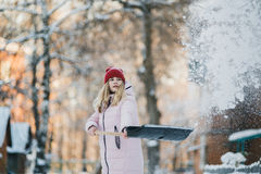 A menina do jovem adolescente limpa a neve perto da casa, guardando uma pá e a pá passa o tempo Fotografia de Stock Royalty Free