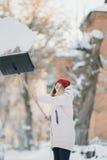 A menina do jovem adolescente limpa a neve perto da casa, guardando uma pá e a pá passa o tempo Foto de Stock Royalty Free