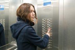 A menina do jovem adolescente no elevador, pressiona o botão do elevador fotos de stock