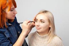 A menina do maquilhador com cabelo vermelho e uma escova em sua mão impõe a composição nos olhos do modelo - máscaras da cor dour fotos de stock royalty free