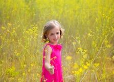 A menina do miúdo da criança no campo de flores do amarelo da mola e o rosa vestem-se Imagens de Stock