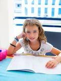 Menina do miúdo que sorri com trabalhos de casa no verão Fotos de Stock