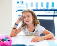 Menina do miúdo que sorri com trabalhos de casa no verão Fotografia de Stock