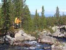 Menina do mochileiro em uma rocha perto do rio que procura a maneira Fotos de Stock