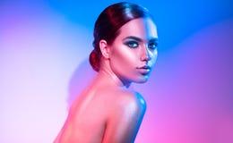 Menina do modelo de alta-costura em sparkles brilhantes coloridos e nas luzes de néon que levantam no estúdio Retrato da mulher b foto de stock