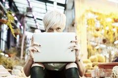 Menina do moderno com o cabelo louro escondido atrás do laptop aberto, sentando-se em escadas em um parque exterior, na luz do so Fotos de Stock Royalty Free