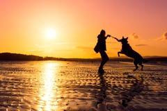Menina do moderno que joga com cão em uma praia durante o por do sol, silhuetas Fotografia de Stock