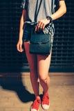 Menina do moderno que levanta na porta de Front Of Closed Night Club em instrutores vermelhos com bolsa preta foto de stock royalty free