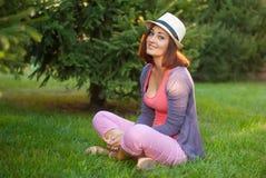 Menina do moderno que senta-se na grama verde Imagem de Stock Royalty Free