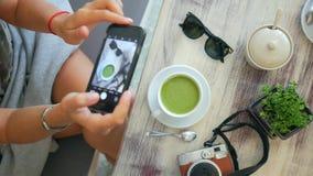 Menina do moderno que toma a foto do Latte do chá verde de Matcha no copo Composição de tabela bonita do estilo de vida no café H filme