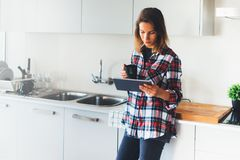 Menina do moderno que usa o café da tecnologia e da bebida da tabuleta na cozinha, foto de stock