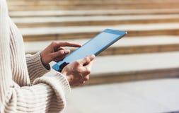 Menina do moderno que usa o Internet da tecnologia da tabuleta, pessoa do blogger que guarda o computador no fundo Sun City, mãos imagens de stock