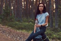 A menina do moderno do turista guarda uma garrafa da água, parada para descansar em uma floresta bonita do outono imagens de stock royalty free