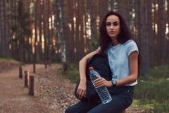 A menina do moderno do turista guarda uma garrafa da água, parada para descansar em uma floresta bonita do outono imagens de stock